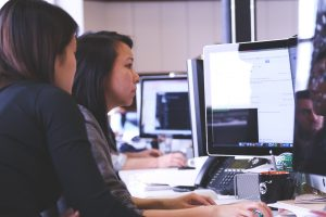 Two women coding together at a coworking space.